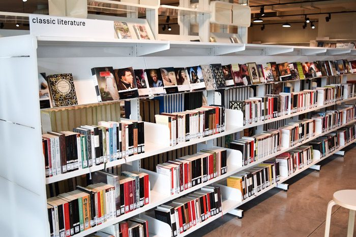 Geelong Library interior, long white shelves are stacked neatly with books. A sign read 'classic literature'.
