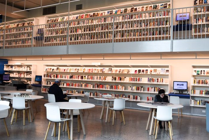 Geelong Library interior, long white shelves are stacked neatly with books on two levels, the upper level with a balcony. Two people sit at white tables in the foreground.