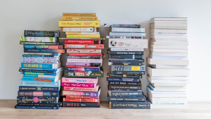 Four stacks of books, arranged by colour. The far right column has books stacked with their pages facing forward